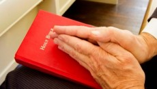 Hands praying over a Bible